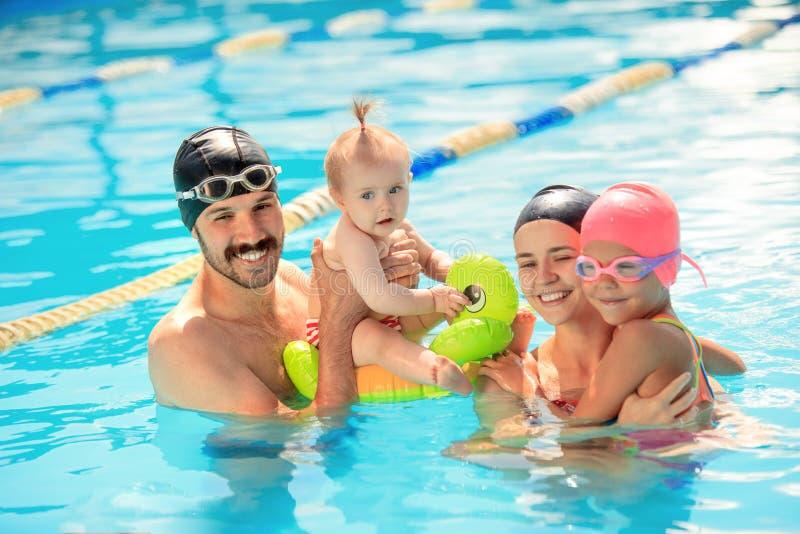 Счастливая семья имея потеху бассейном стоковые фото