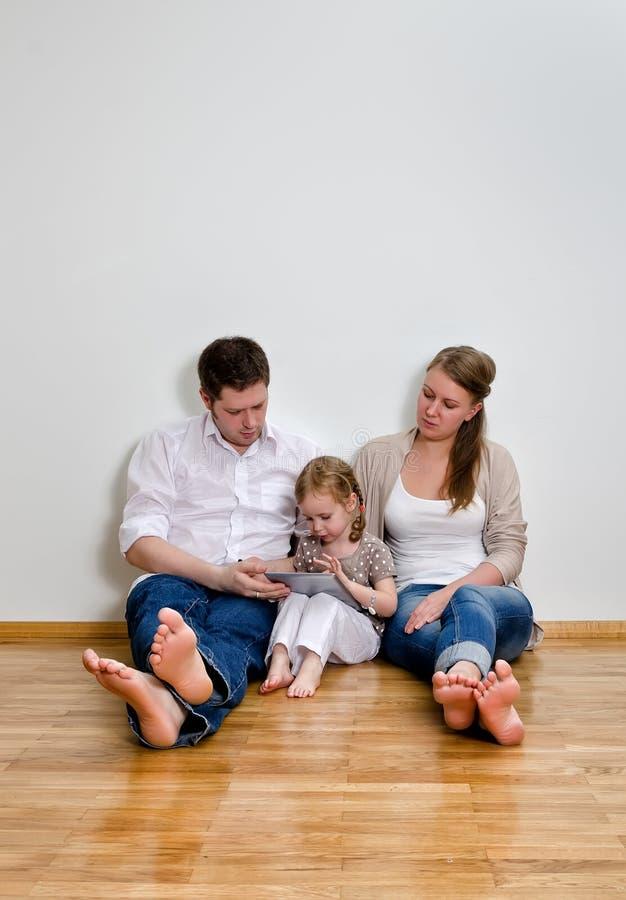 Счастливая семья используя компьютер таблетки стоковые фото