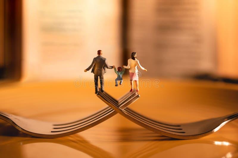 Счастливая семья и концепция баланса жизни работы Миниатюра отца, матери и сына держа руки и идя на вилку стоковое изображение