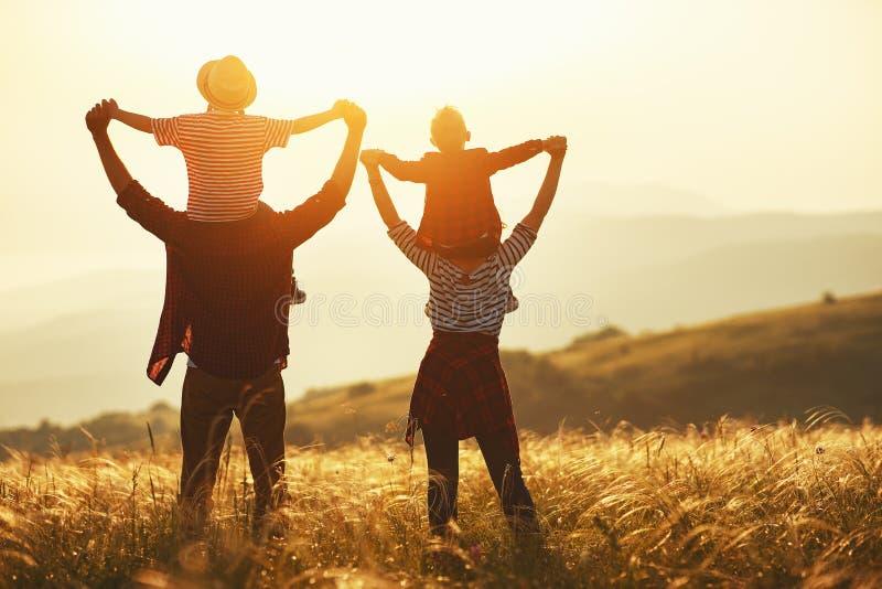 Счастливая семья: мать, отец, дети сын и дочь на заходе солнца стоковое фото