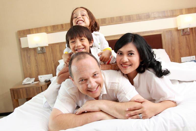 Счастливая семья на белой кровати стоковые фото