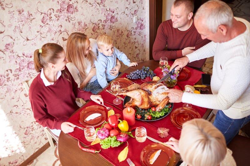 Счастливая семья на обеденном столе празднуя благодарение на запачканной предпосылке Традиционная концепция благодарения стоковое фото