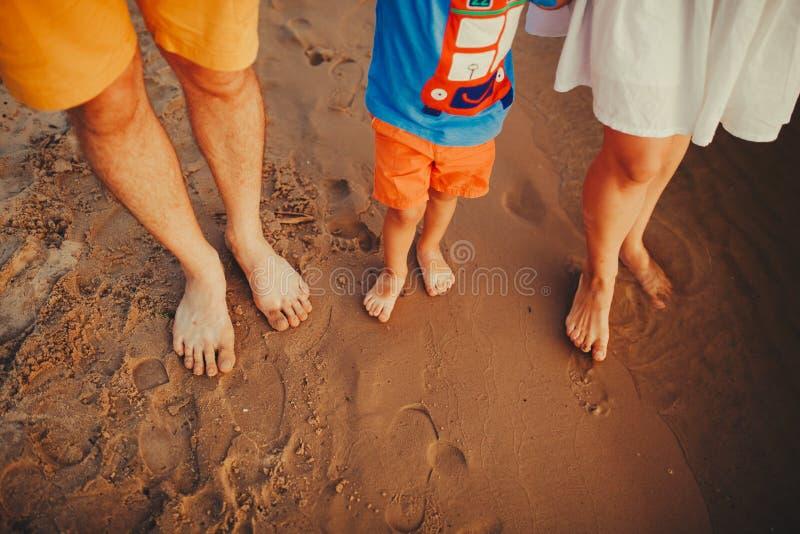 Счастливая семья на пляже Крупный план ног семьи с младенцем мальчика идя на песок Человек и женщина держа их младенца Прогулка  стоковые фото