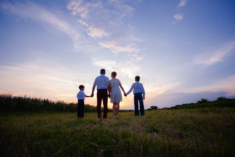 Счастливая семья на предпосылке захода солнца стоковые фото