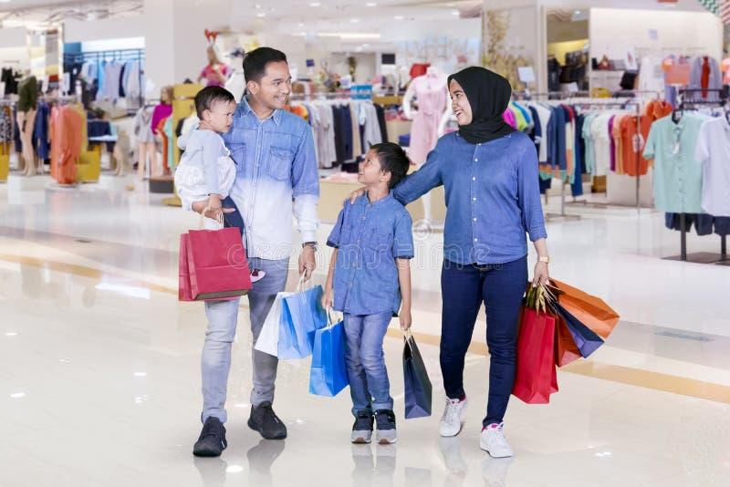 Счастливая семья носит хозяйственные сумки в торговом центре стоковые изображения rf