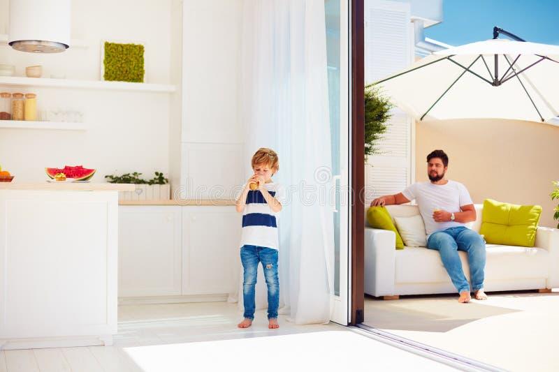 Счастливая семья ослабляя на патио крыши с кухней открытого пространства на теплом летнем дне стоковые фотографии rf