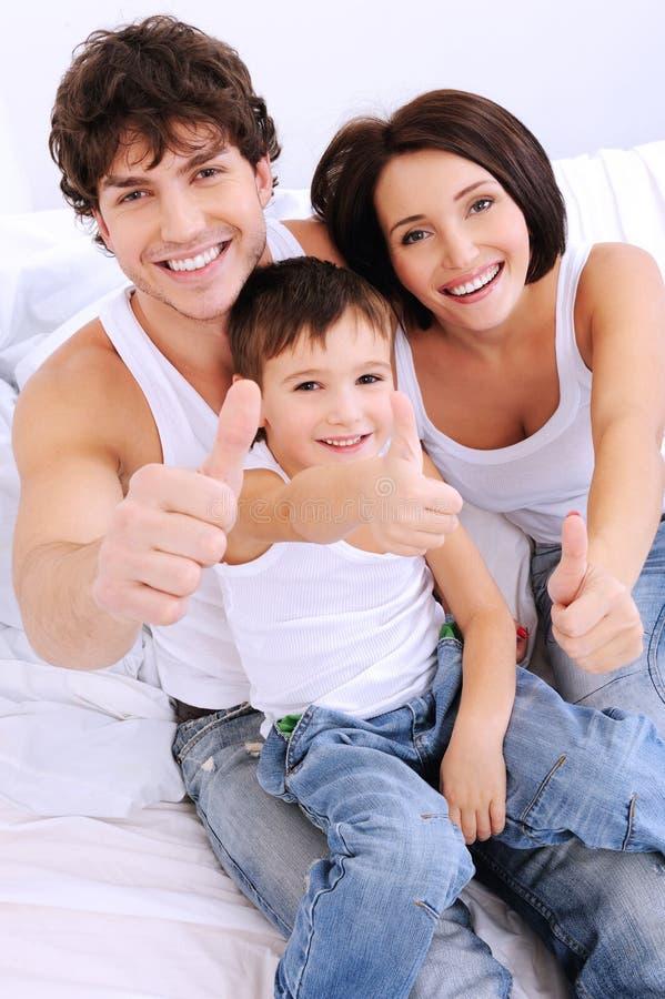 Счастливая семья показывая жест thumbs-up
