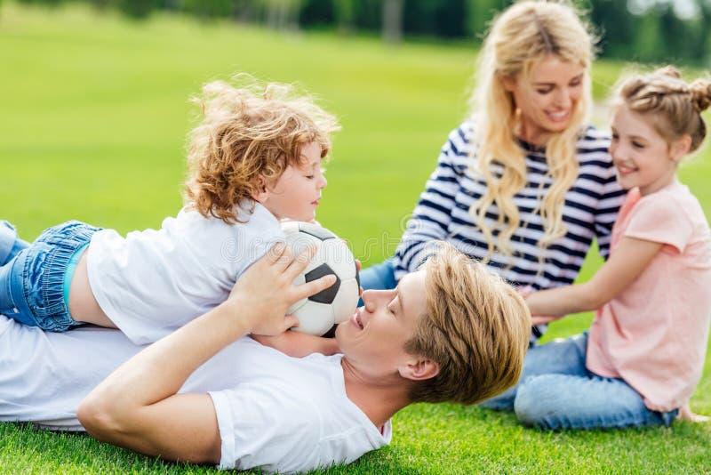 счастливая семья при 2 дет имея потеху с футбольным мячом пока лежащ стоковые фотографии rf