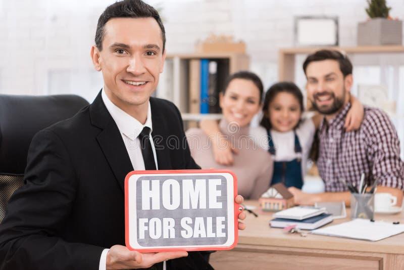 Счастливая семья сидит на таблице риэлтора который держит знак с надписью расквартируйте сбывание стоковые фото