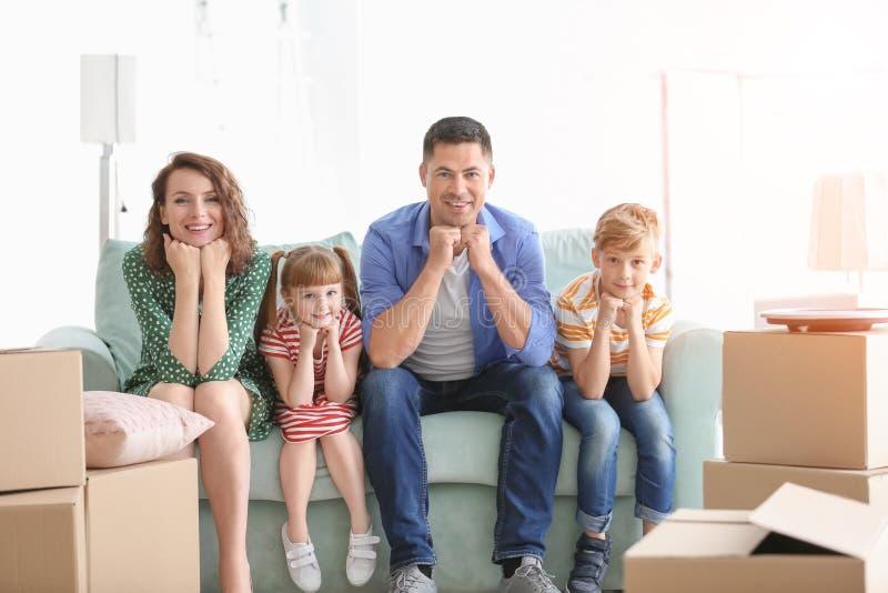 Счастливая семья сидя на софе около коробок внутри помещения Двигать в новый дом стоковые изображения