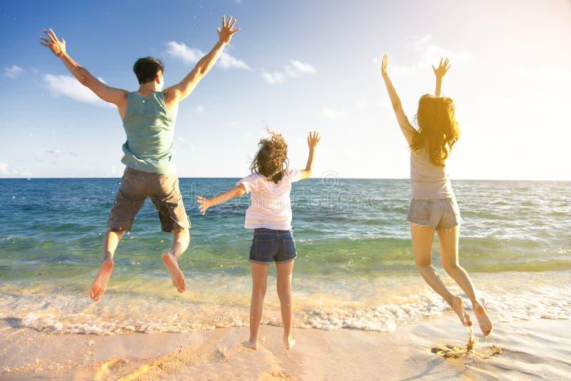 Счастливая семья скача на пляж стоковое фото rf