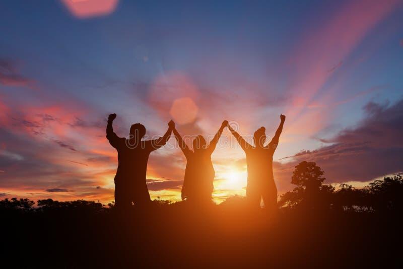 Счастливая семья стоя в заходе солнца стоковые изображения rf
