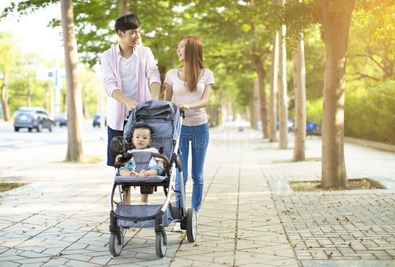 Счастливая семья с детской дорожной коляской идя в парк стоковые изображения