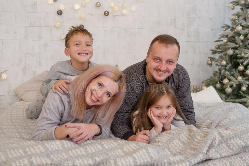 Счастливая семья с 2 детьми под лежать рождественской елки стоковая фотография rf