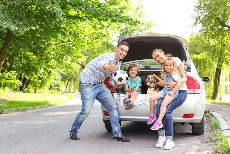 Счастливая семья с милой собакой около автомобиля outdoors стоковые изображения rf