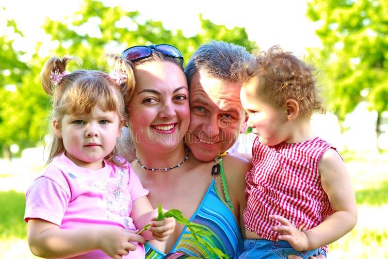 Счастливая семья с 2 дочами outdoors стоковые изображения
