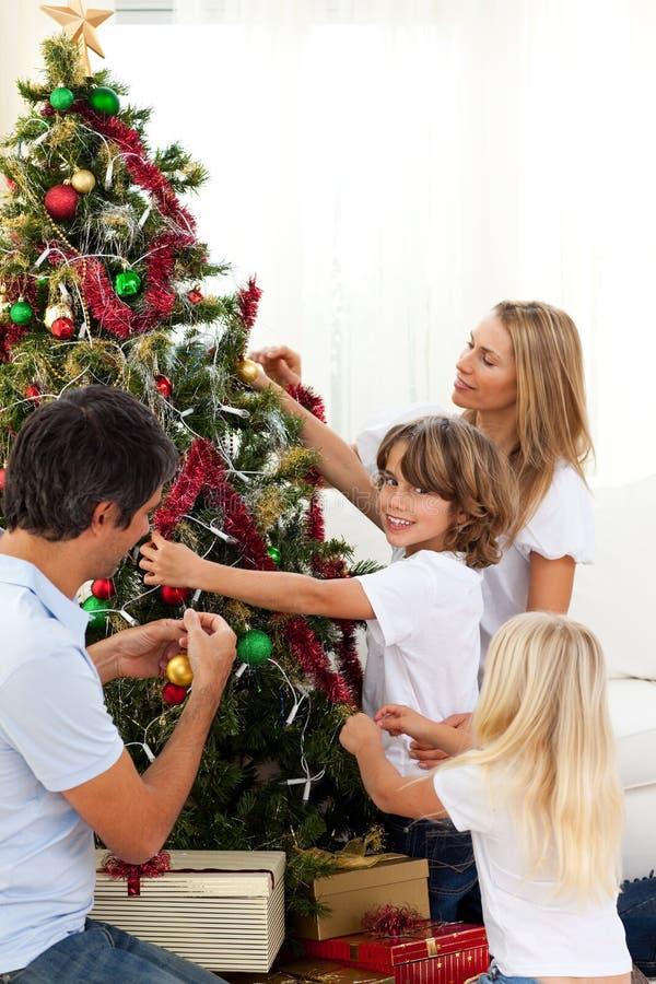 Счастливая семья украшая рождественскую елку стоковое изображение rf