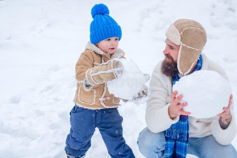Счастливая семья plaing со снеговиком на снежной прогулке зимы Отец и сын делая снежный ком на предпосылке зимы белой стоковые фотографии rf