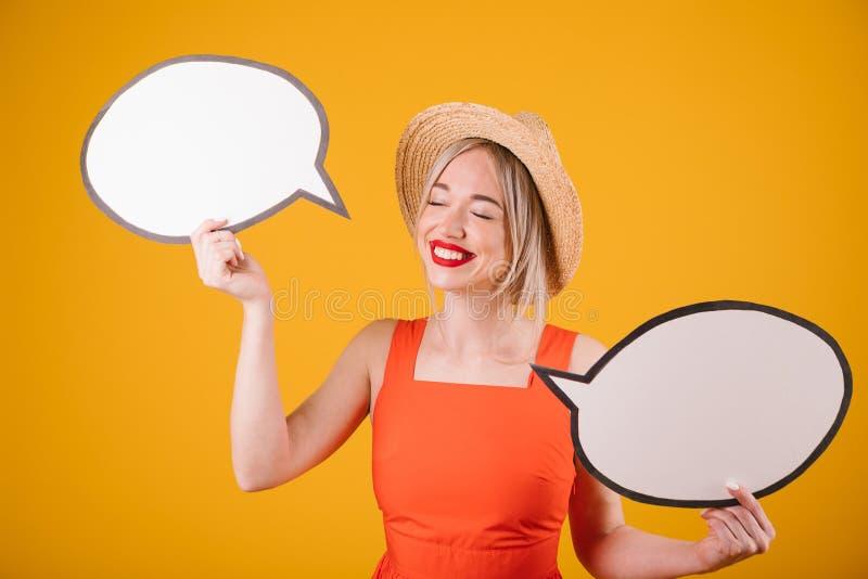 Счастливая симпатичная белокурая девушка в соломенной шляпе и красном причудливом платье держит знамена речи buble Желтая предпос стоковая фотография
