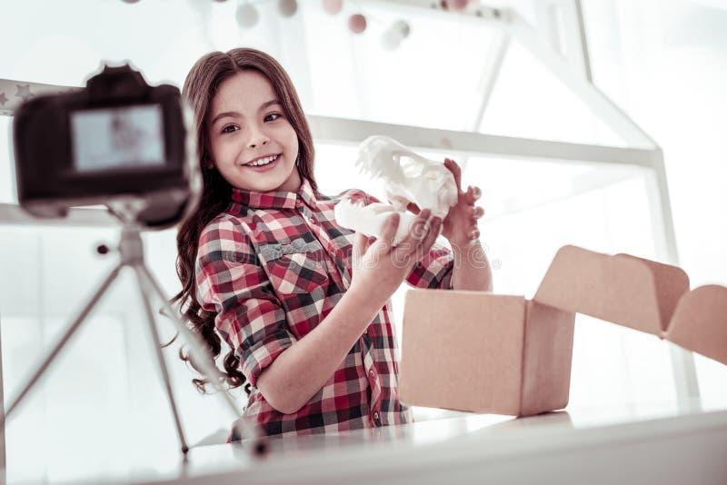 Счастливая славная девушка показывая череп динозавра стоковое фото rf