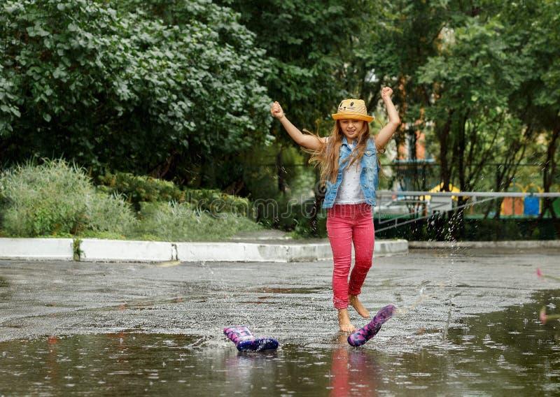Счастливая смешная маленькая девочка скача на лужицы в резиновых ботинках и смеяться стоковое фото