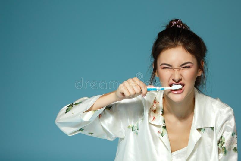 Счастливая смешная предназначенная для подростков щетка девушки ее зубы Тема утра стоковые фотографии rf