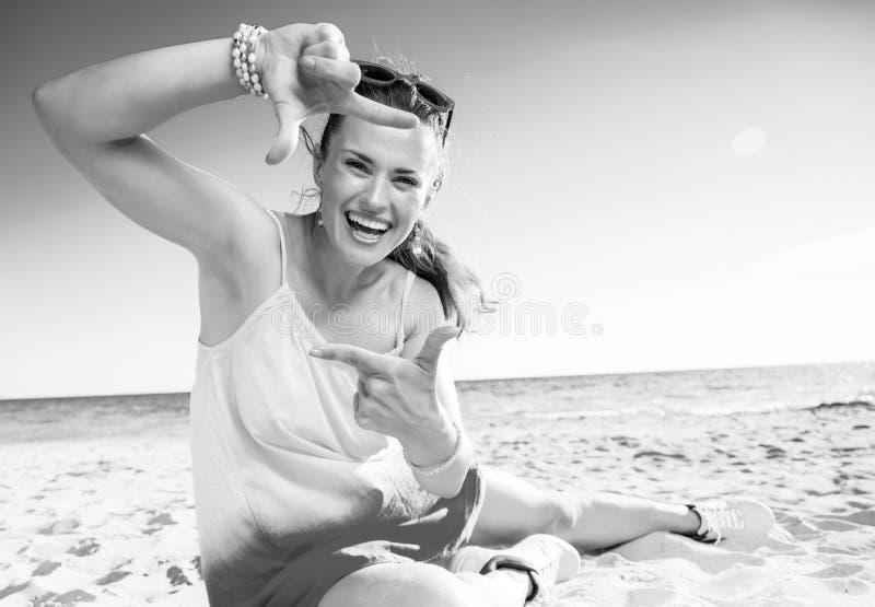 Счастливая современная женщина на пляже обрамляя с руками стоковые фото