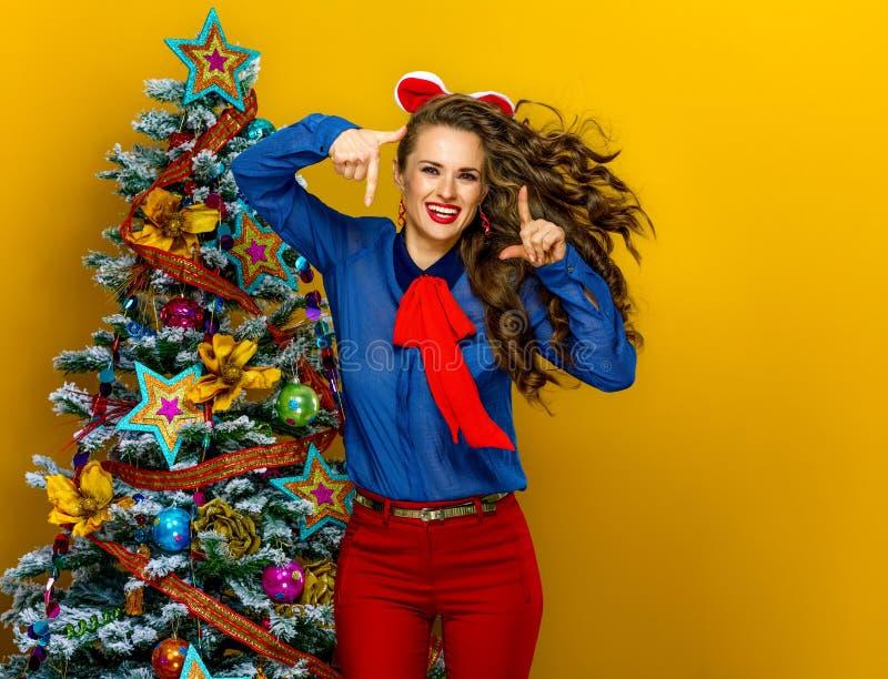 Счастливая современная женщина около рождественской елки обрамляя с руками стоковое изображение rf