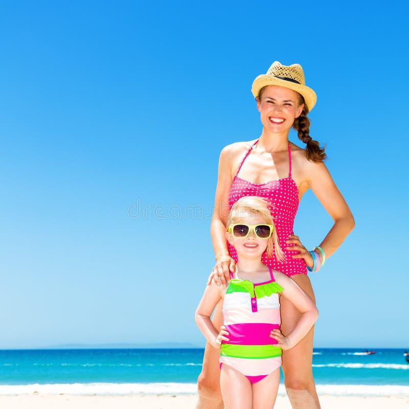 Счастливая современные мать и дочь стоя на seashore стоковое фото rf