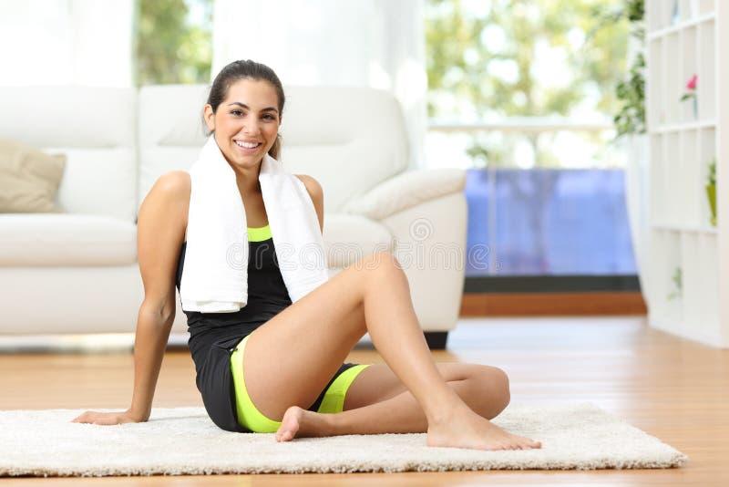 Счастливая спортсменка представляя дома после тренировки стоковое изображение rf