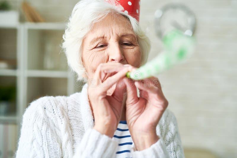 Счастливая старшая дама на партии стоковая фотография