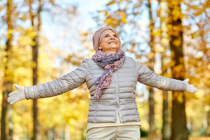 Счастливая старшая женщина наслаждаясь красивой осенью стоковые фотографии rf