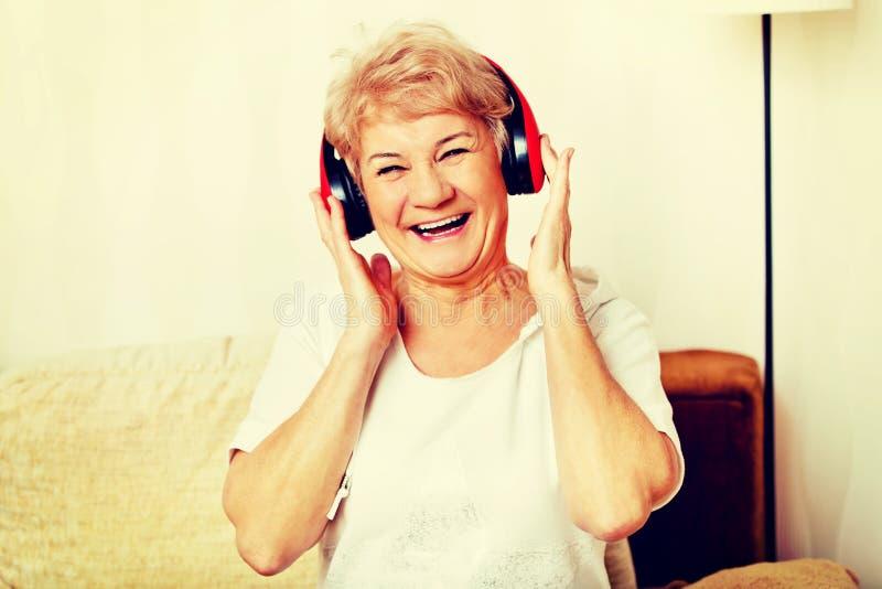 Счастливая старшая женщина нося красные наушники стоковая фотография