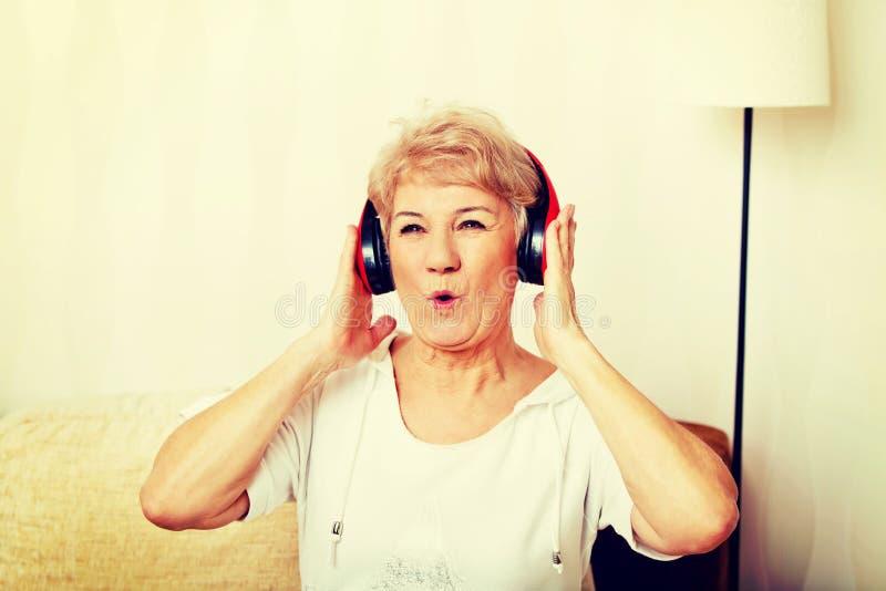 Счастливая старшая женщина нося красные наушники стоковые изображения
