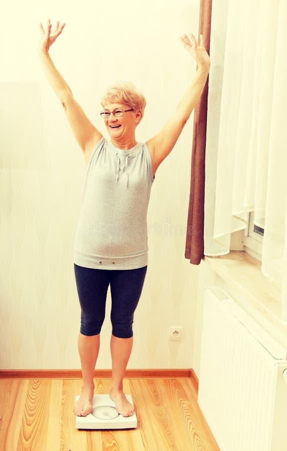 Счастливая старшая женщина стоя на масштабе веса в живущей комнате стоковое фото