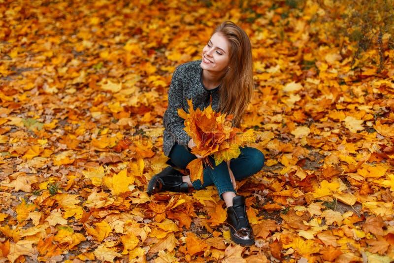 Счастливая стильная молодая женщина в джинсах в ультрамодном пальто в ботинках сидя на том основании среди желтой листвы и держа  стоковое изображение rf