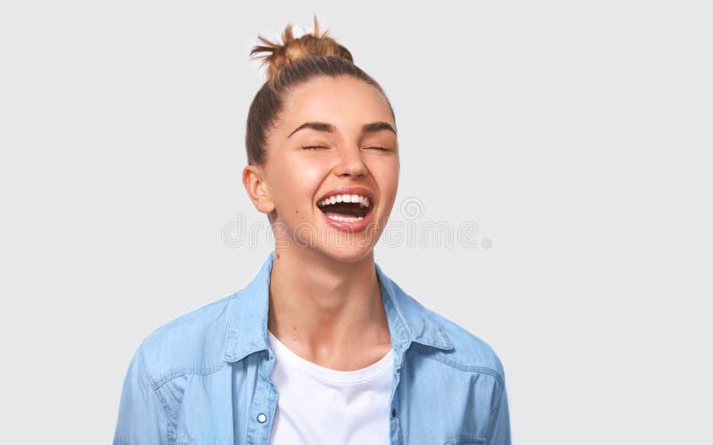 счастливая студентка с булочными волосами, улыбающаяся положительно и находящаяся в хорошем настроении, стоя на фоне белой студии стоковое изображение rf