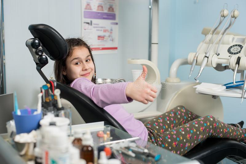 Счастливая терпеливая девушка показывая большие пальцы руки вверх на зубоврачебном офисе Концепция медицины, стоматологии и здрав стоковые фотографии rf