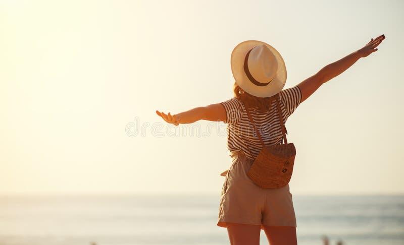 Счастливая туристская девушка с рюкзаком и шляпой на море стоковая фотография rf