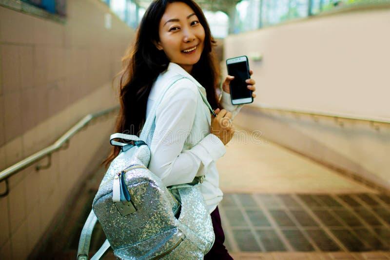 Счастливая улыбка азиатской женщины по телефону на улице города стоковые фото