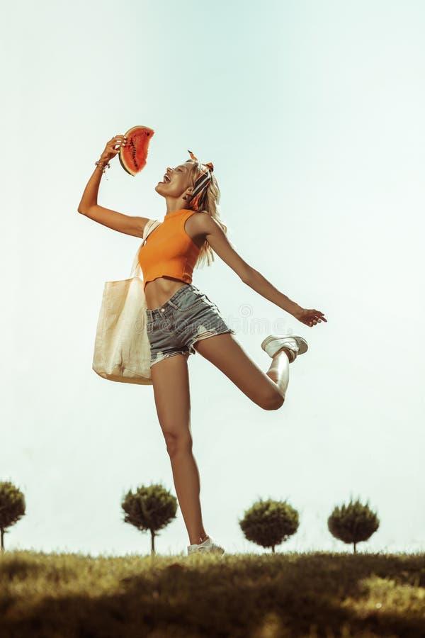 Счастливая умоляющая заколдовывая женщина скача вверх с арбузом стоковые изображения