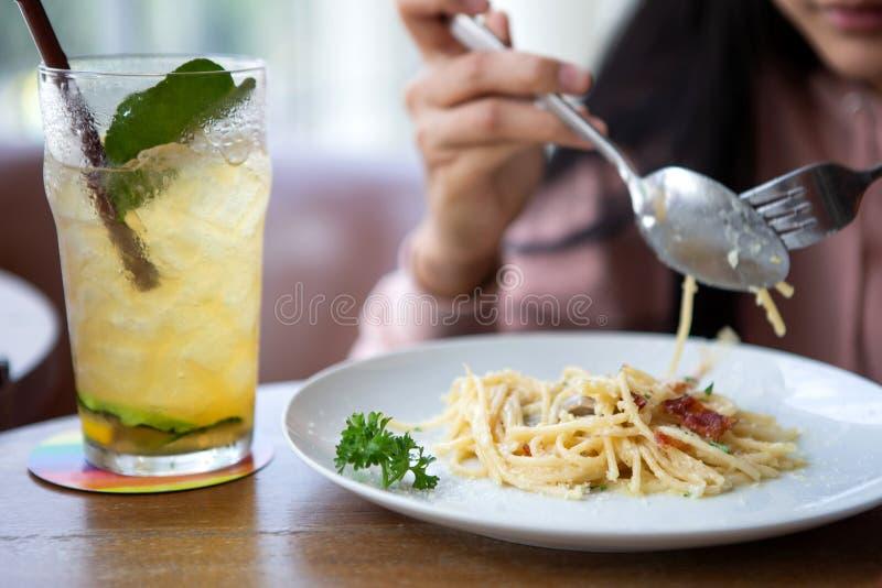 Счастливая усмехаясь азиатская женщина есть итальянские макаронные изделия с лимонадом в ресторанах r стоковые изображения rf