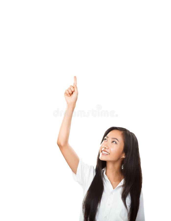 Счастливая усмехаясь азиатская женщина указывая вверх и смотря камеру стоковое изображение rf