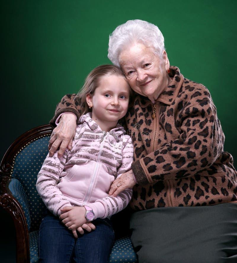 Счастливая усмехаясь бабушка и внучка представляя в студии стоковое фото