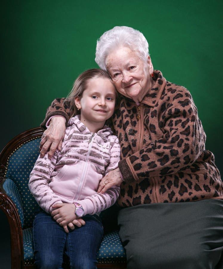 Счастливая усмехаясь бабушка и внучка представляя в студии стоковые изображения