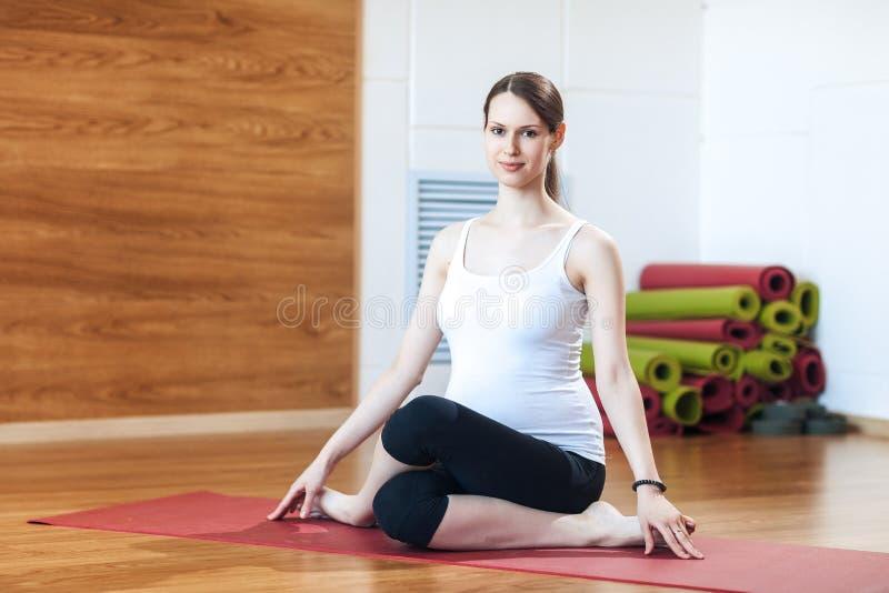 Счастливая усмехаясь беременная женщина сидя в представлении лотоса практикуя йога женщины стоковые изображения rf