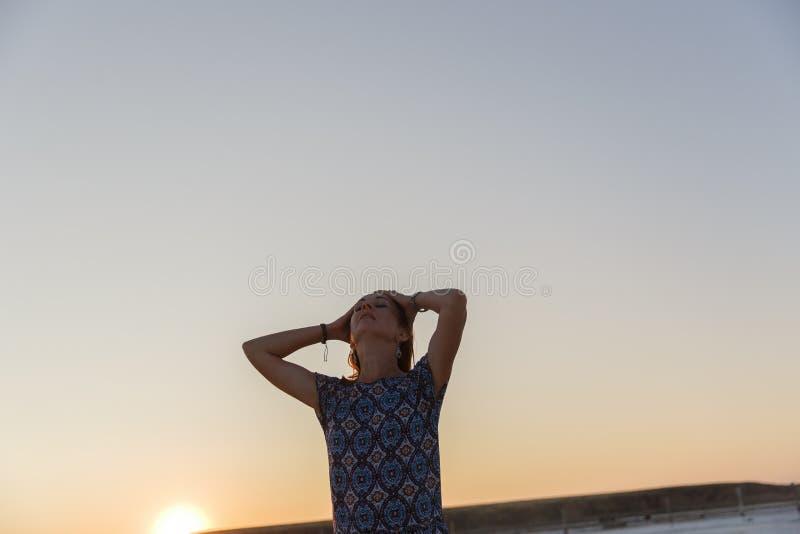 Счастливая усмехаясь девушка в белой шляпе наслаждаясь солнцем, ширью озера соли Bascunchak стоковое фото