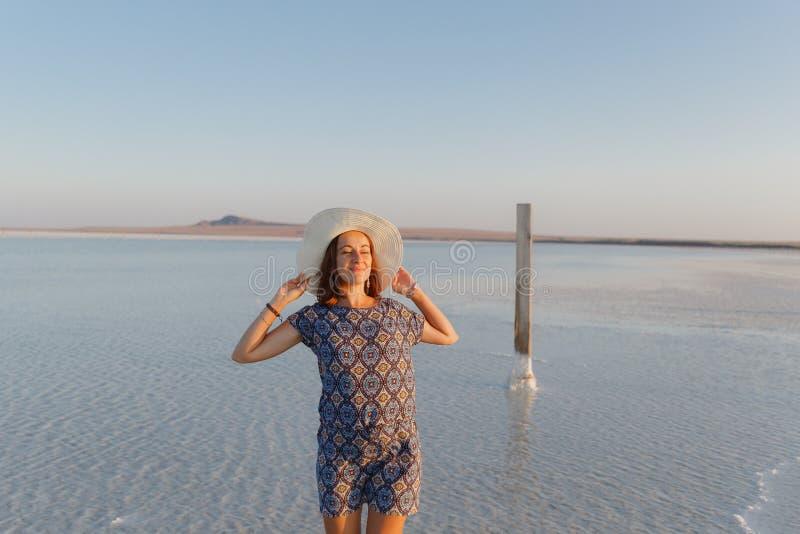 Счастливая усмехаясь девушка в белой шляпе наслаждаясь солнцем, ширью озера соли Bascunchak стоковые изображения rf