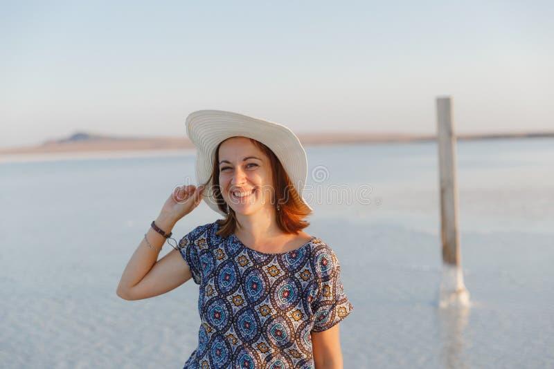 Счастливая усмехаясь девушка в белой шляпе наслаждаясь солнцем, ширью озера соли Bascunchak стоковое изображение rf