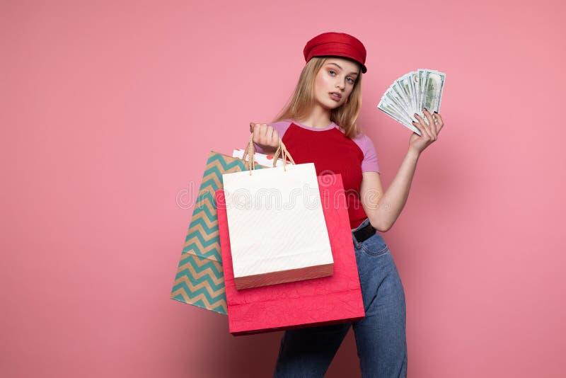 Счастливая усмехаясь девушка в ультрамодной красной шляпе держа красочные хозяйственные сумки стоковое изображение rf